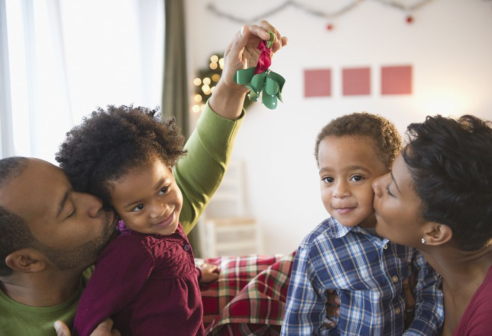 Black father holding mistletoe over daughter's head