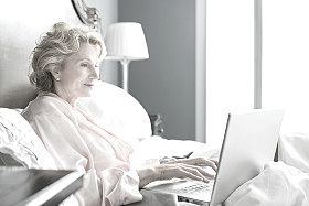 Woman using her computer in bed.