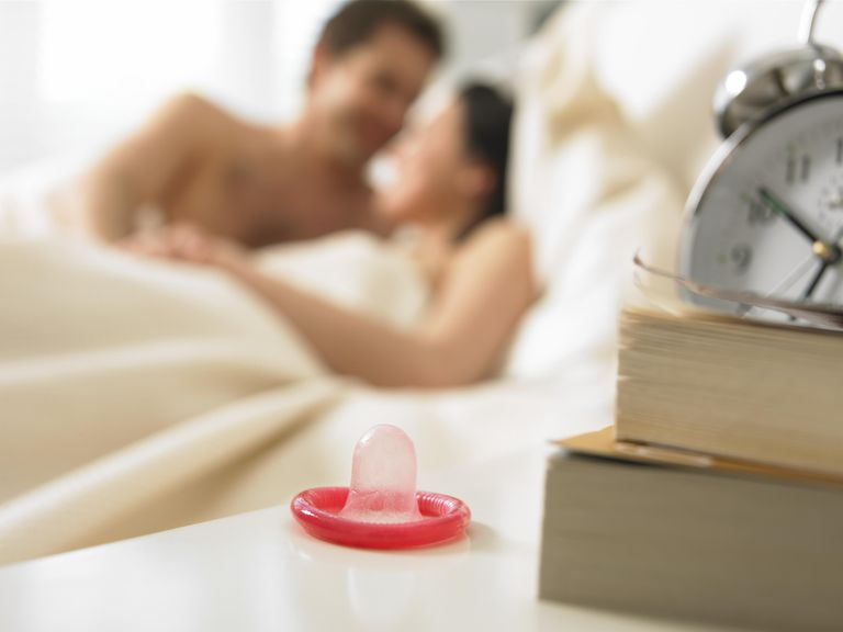 Couple embracing in bed, focus on condom in foreground