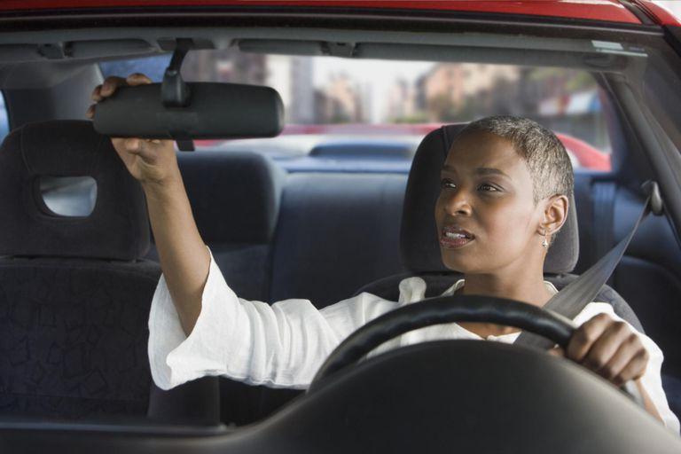 African woman in car adjusting mirror