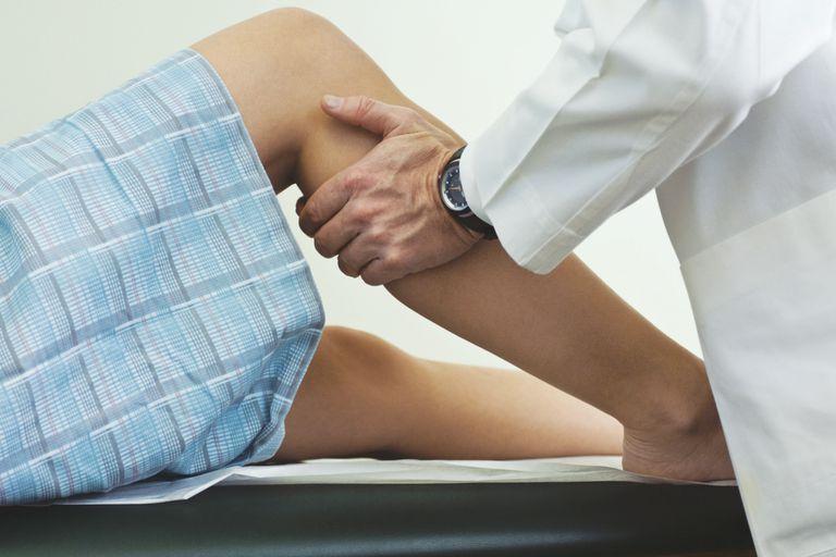 Doctor examining woman's calf