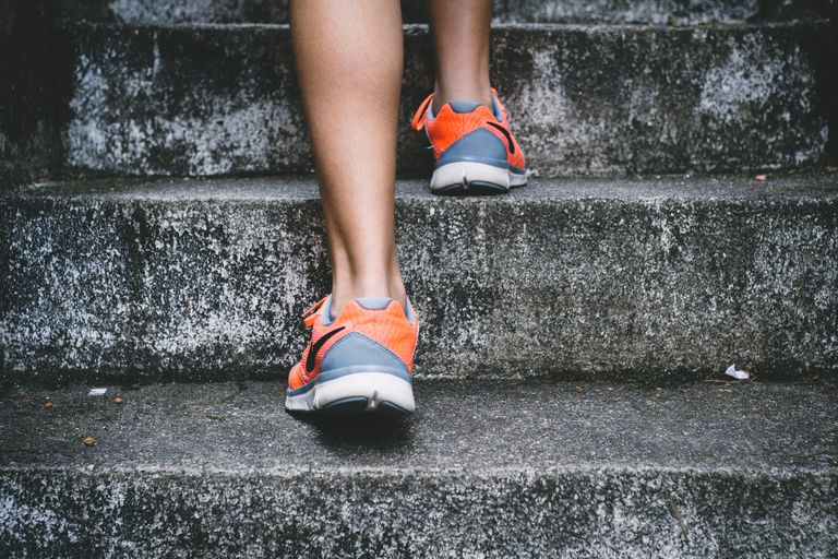 Person wearing gym sneakers climbing stairs