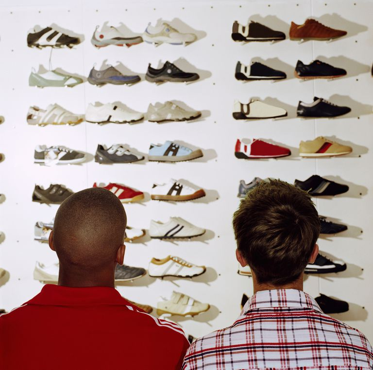 Two teenage boys (15-17) looking at trainers in sports shop, rear view