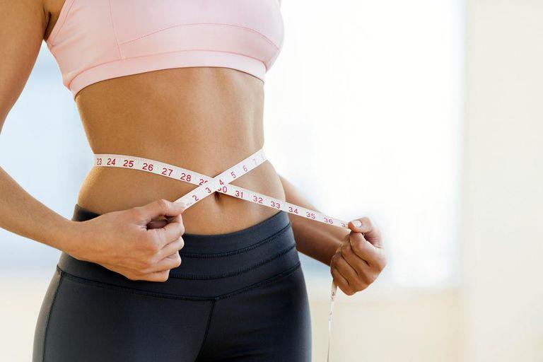 USA, New Jersey, Jersey City, Woman measuring waist
