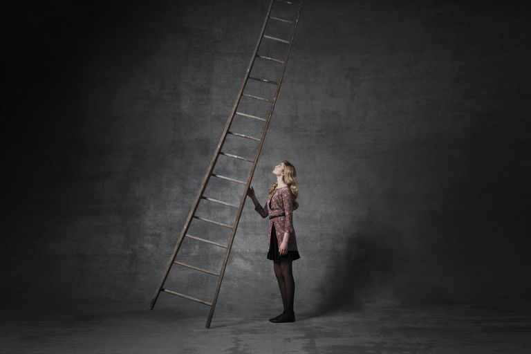Business woman holding ladder