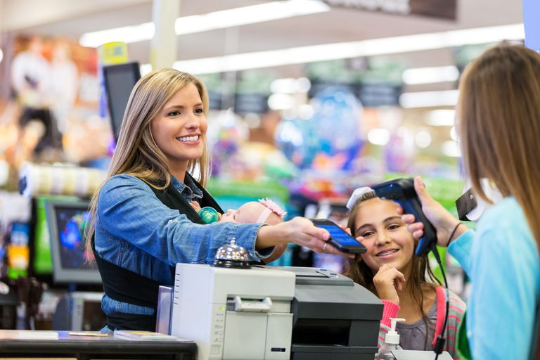 Mother using smart phone to pay for purchases in store