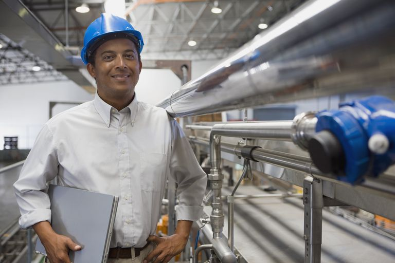 Manager holding laptop in factory