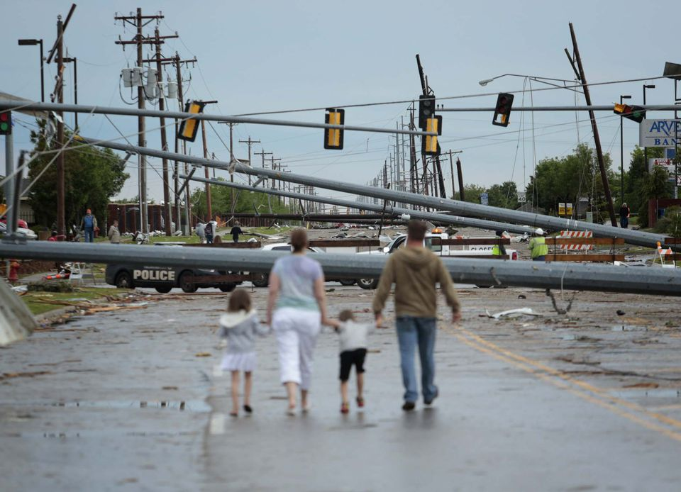 A picture of a family walking down the street after a tornado