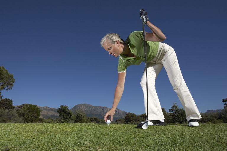 Woman placing golf ball onto tee