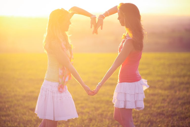 Two girls making heart shape with their armas and hands in sunset, summer.