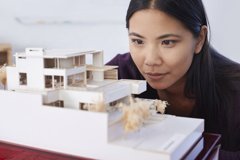A patience young woman excitedly gazing at a built architectural model