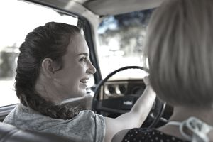 Woman in drivers seat, laughing to friend
