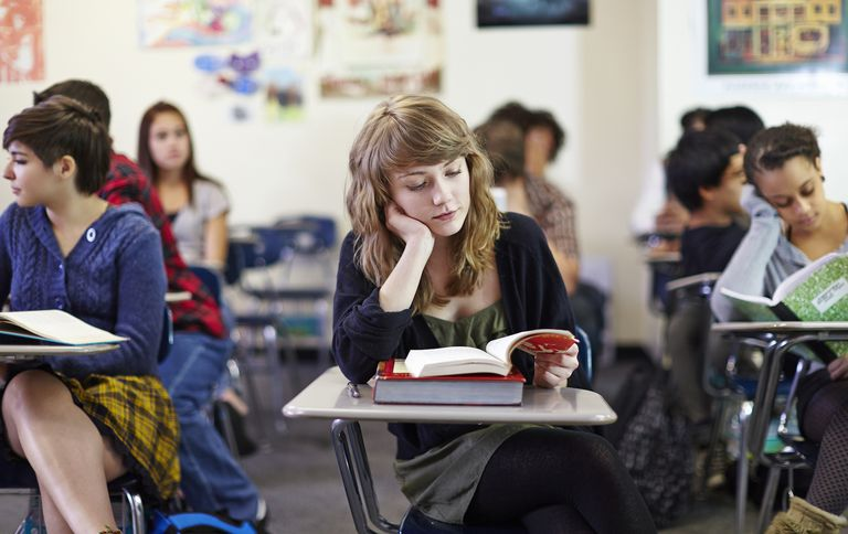 Teenage student in middle of classroom reading.