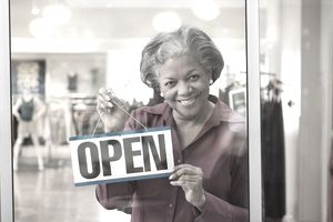 Small business owner with an open sign.
