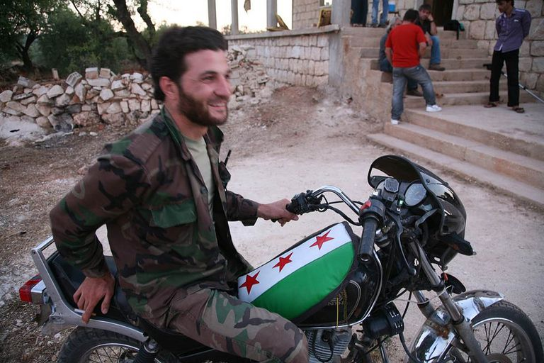 Rebel Commander Ahmad Bakran sits on his rebel flag-adorned motorcycle in the village of Mghara, Syria.