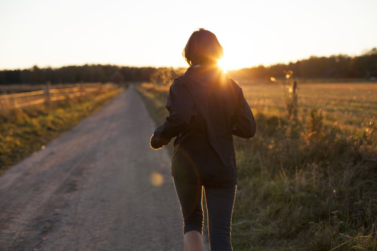 Woman jogging on trail into sunrise, new resolution for her fertility