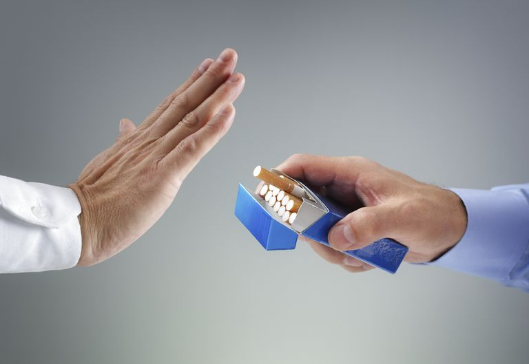 man holding up a hand saying no to a pack of cigarettes