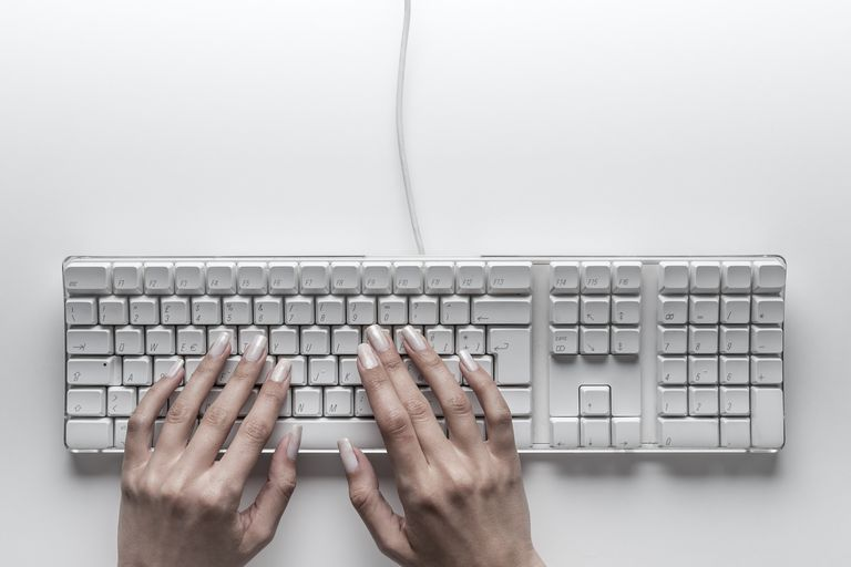 Beautiful girl hands typing on computer keyboard