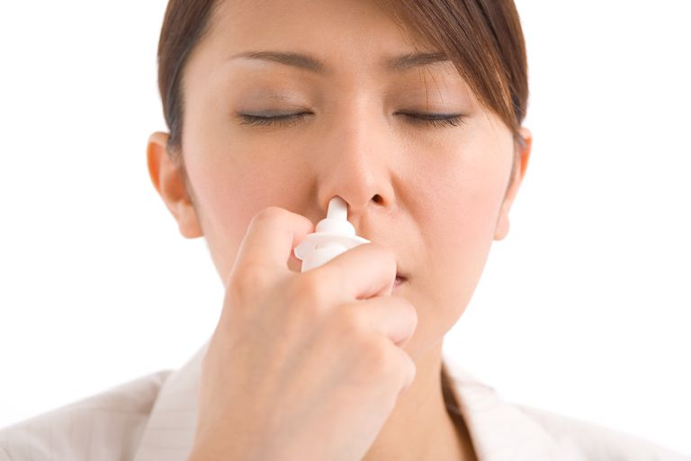 A young woman using nasal spray