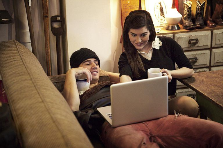 Young Couple Playing on Laptop With Hot Drinks