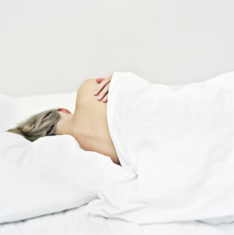 Rear view of woman sleeping on the bed