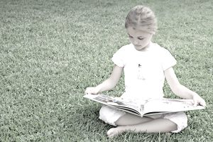 Young Girl Sitting on Grass Reading a Book