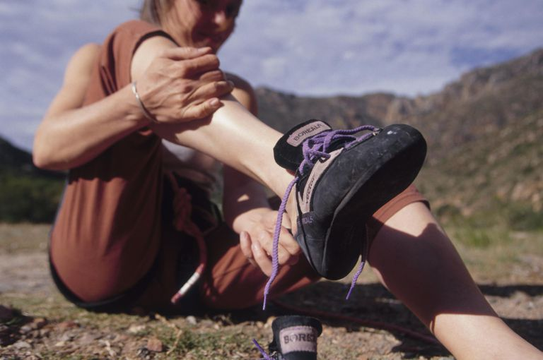 Woman Putting on Climbing Shoe