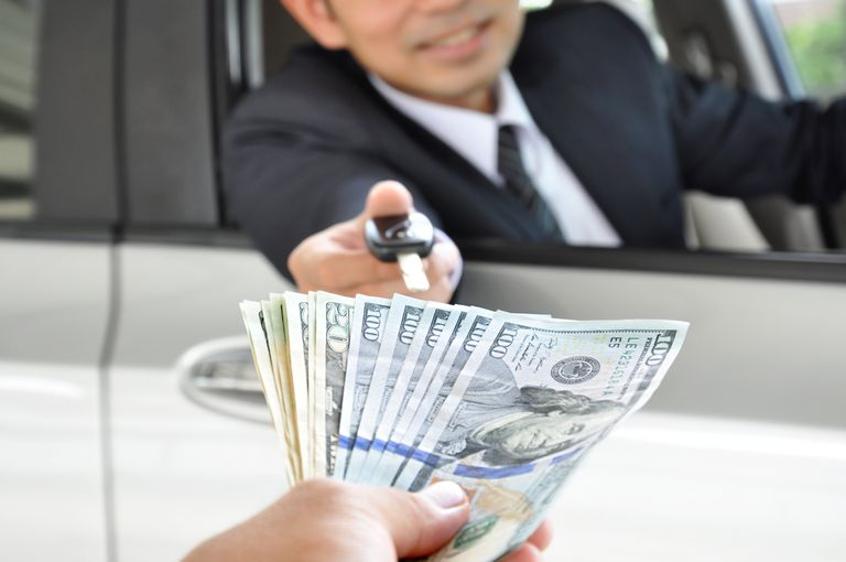 Businessman giving a car key, exchanging for money