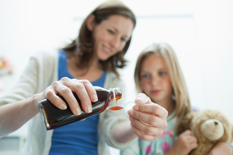 Mother giving sick daughter medicine