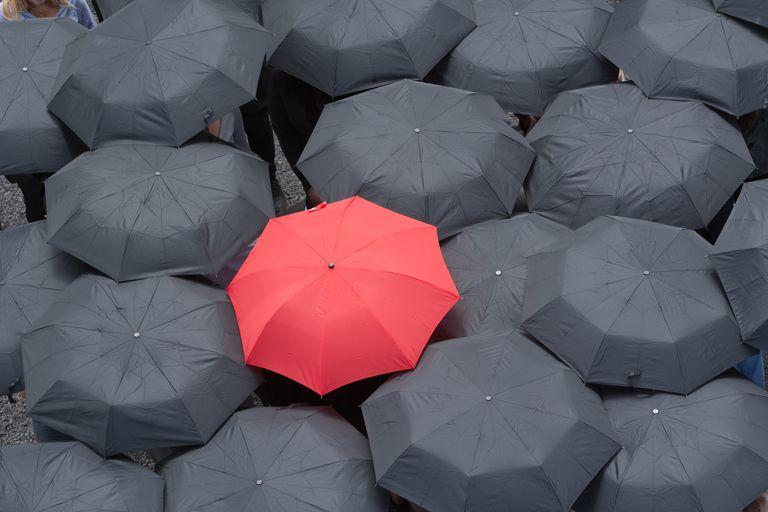 One red umbrella at center of multiple black umbrellas