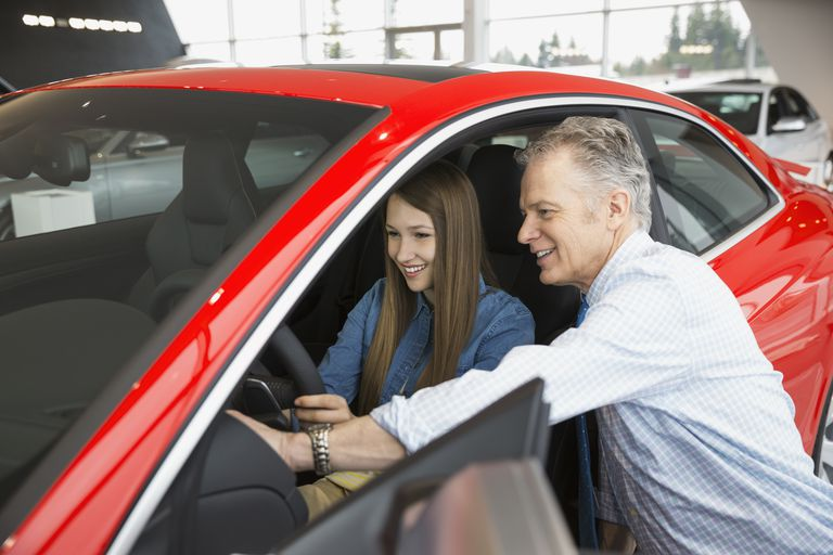 Salesman and woman looking inside car in showroom