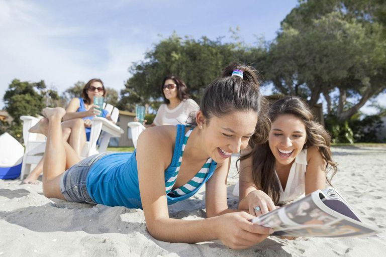 Sisters lying on beach reading magazine with mom and aunt in background