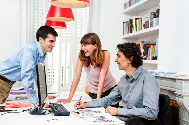 Two men and one woman smiling at office table