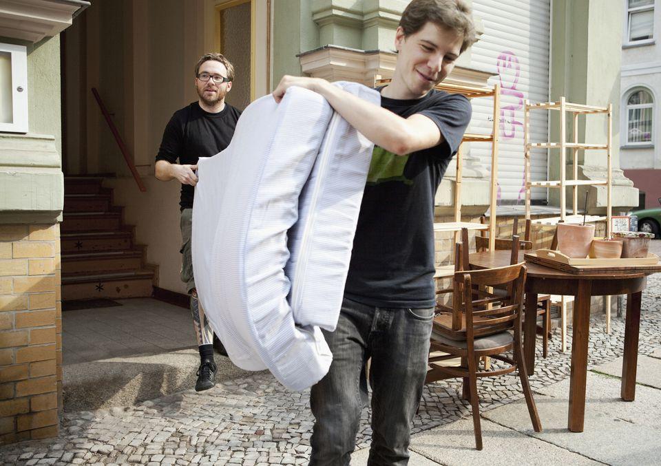 Men carrying mattress