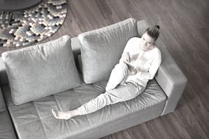 Woman sitting on couch in home