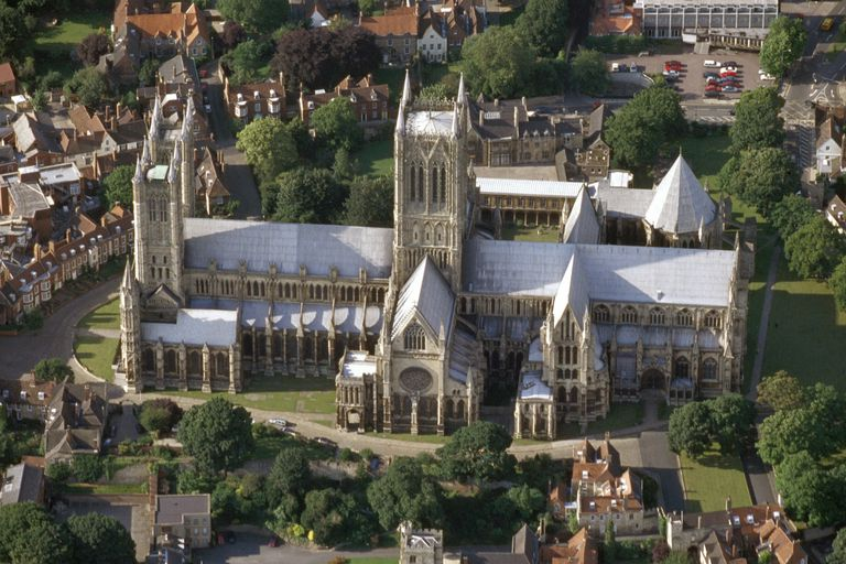 Aerial view of Gothic style Lincoln Cathedral in Lincolnshire, England, surrounded by houses and trees. The various architectural features such as towers, spire, windows and flying buttresses can be seen.