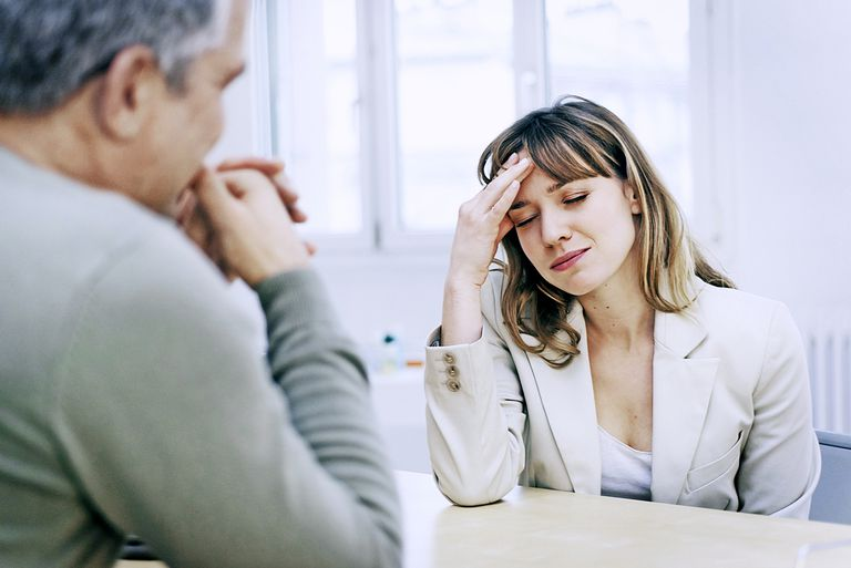 Woman with headache, talking with Doctor