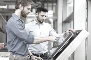 Two businessmen using touchscreen equipment