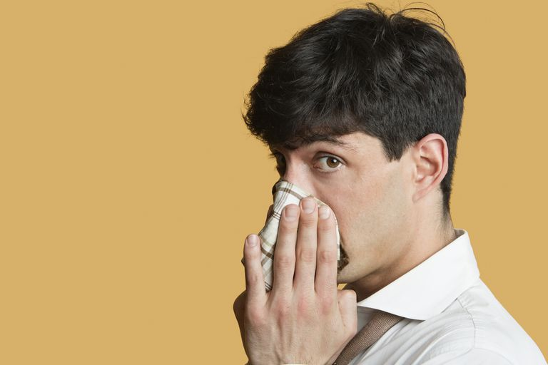 Portrait of a man blowing his nose over colored background