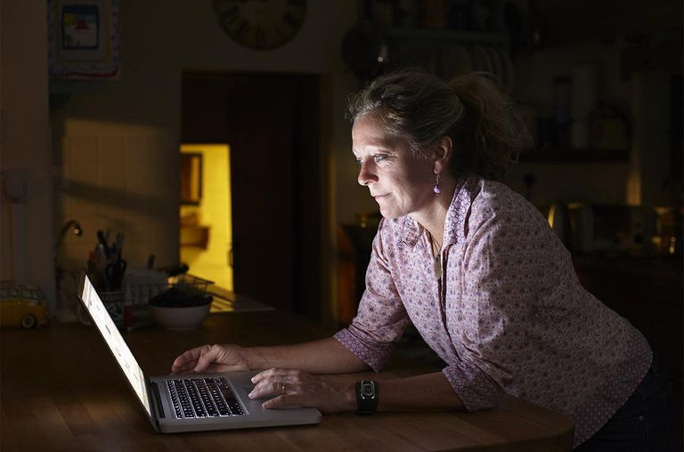 Woman using laptop in kitchen at night