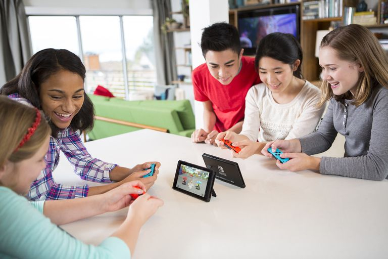People gathered around the Nintendo Switch playing Mario Kart