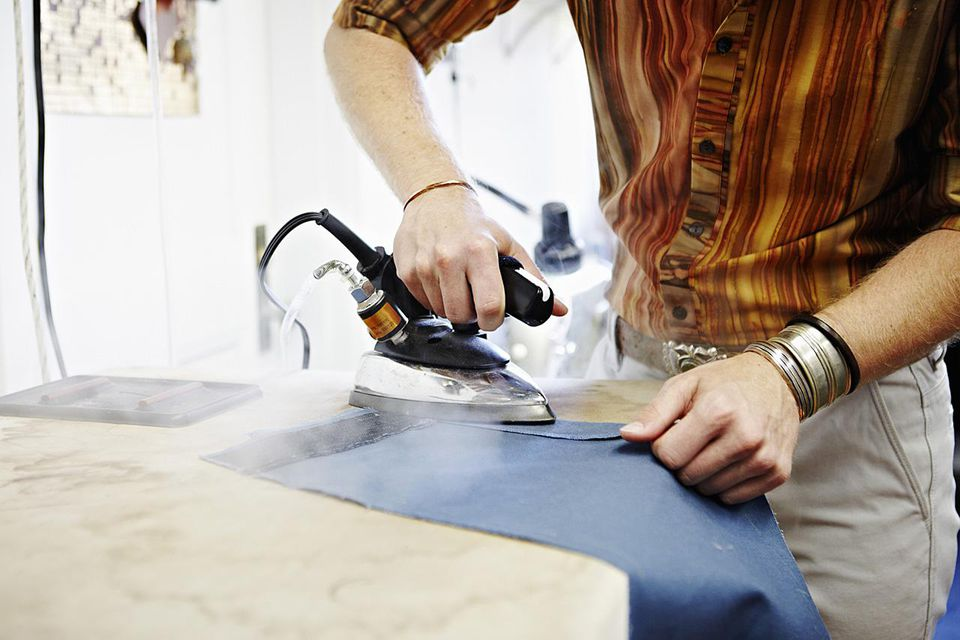 Male fashion designer ironing fabric in studio