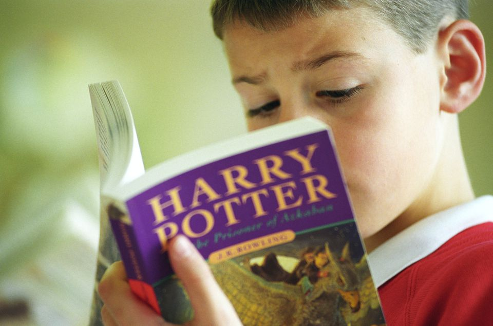 Young boy reading Harry Potter