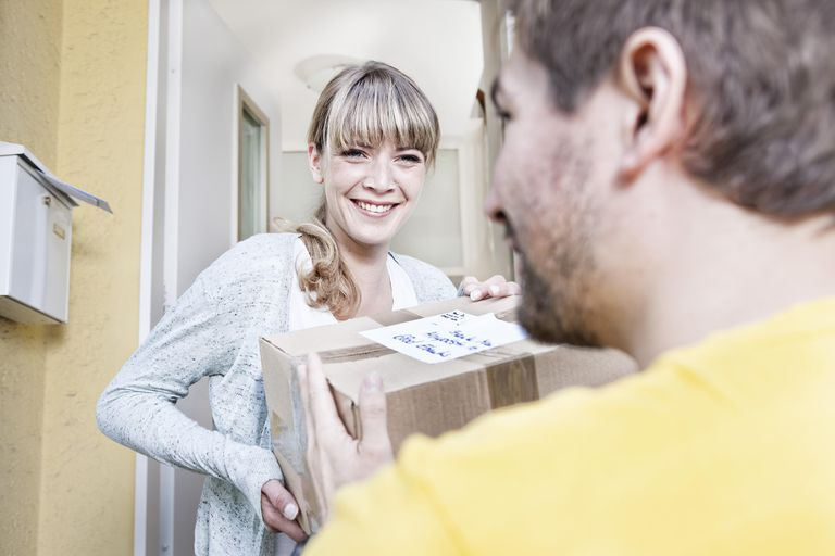 Young woman taking package from delivery