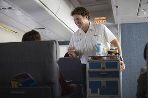 Flight attendant serving passengers on airplane