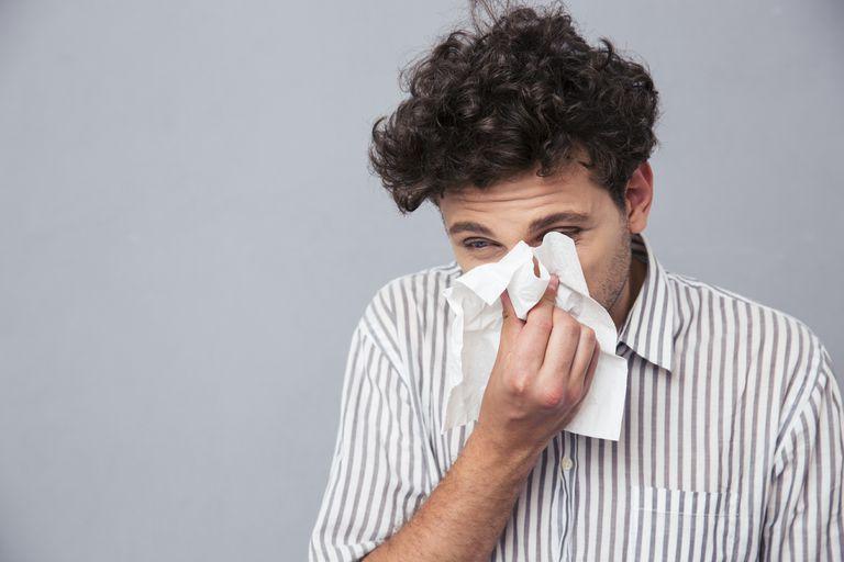 man spitting phlegm into a tissue