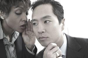Businesswoman telling secret to businessman