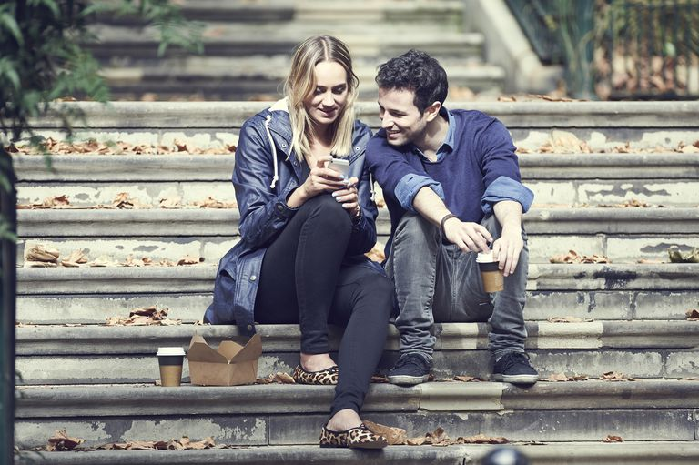 Couple looking at phone outside