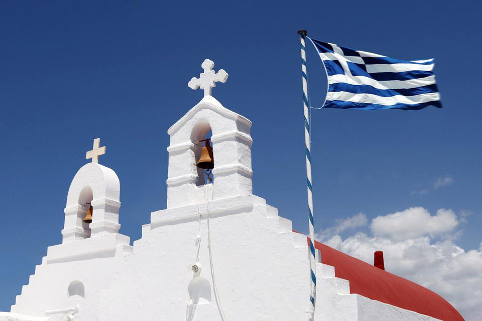 Two white church towers with Greek flag in Mykonos