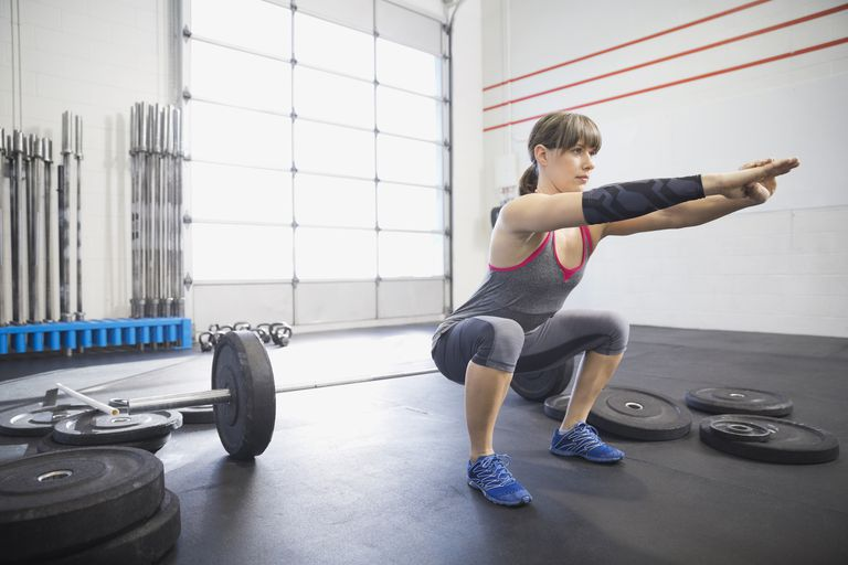 Woman doing squats in a gym